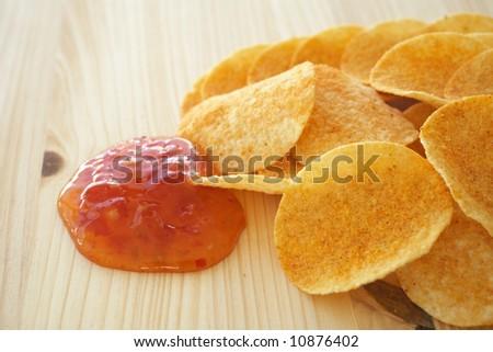 Crispy golden brown potato chips with a hot salsa dip sauce on a wooden presentation plate (shallow depth of field)