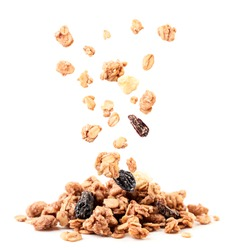 Crispy granola with raisins and banana falling on a heap close-up on a white background. Isolated