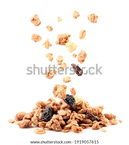 Crispy granola with raisins and banana falling on a heap close-up on a white background. Isolated Stock photo ©