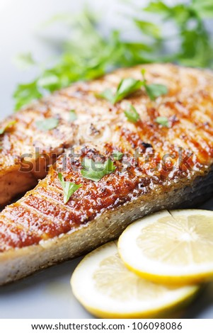 crispy grilled salmon steak with cherry tomatoes and parsley - stock photo