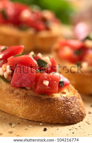 Crispy Italian antipasto  Bruschetta with tomato, garlic, basil on wooden board (Selective Focus, Focus on the front upper edge of the bruschetta and the lower part of the tomato pieces in the front)