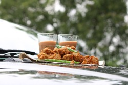 Crispy moong pakora, delicious street food, favourite indian snack in monsoon serve with Hot Tea. Kept on car's bonnet