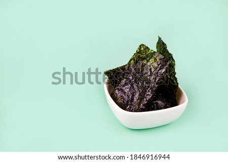 Crispy nori seaweed in bowls on green background. Japanese   Traditional japanese dry seaweed sheets.
