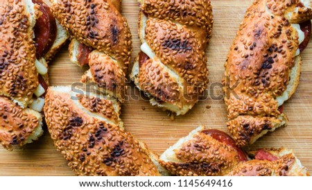 Crispy or crunchy Turkish Bagel Simits on the wooden table. The simit toasts made with sausages and cheddar cheese. Obesity and hungry concept. Gaining height. Diet. Turkish pretzel with sesame.