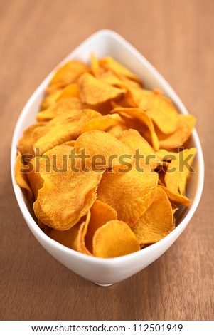 Crispy Peruvian sweet potato chips in white ceramic  bowl on wood (Selective Focus, Focus one third into the sweet potato chips)