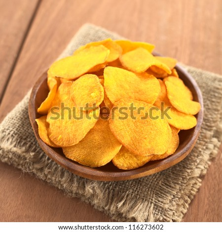 Crispy Peruvian sweet potato chips on wooden plate (Selective Focus, Focus on the lower part of the sweet potato chips)