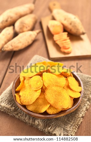 Crispy Peruvian sweet potato chips on wooden plate with sweet potatoes in the back (Selective Focus, Focus one third into the sweet potato chips)