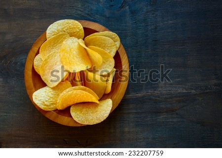 Crispy potato chips in bowl on wooden background, top view