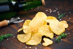 Crispy potato chips with dill and beer bottle