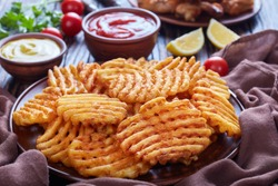 Crispy Potato Criss Cross Fries on a clay plates on a wooden table with mustard and tomato sauce dipping and sticky chicken wings at the background, view from above, close-up