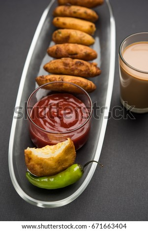 Crispy Potato Pakora OR Aloo Pakoda OR Batata Bhajji served with tomato ketchup, green fried chilly and hot tea, Popular indian all time snack, selective focus #671663404
