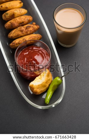 Crispy Potato Pakora OR Aloo Pakoda OR Batata Bhajji served with tomato ketchup, green fried chilly and hot tea, Popular indian all time snack, selective focus #671663428