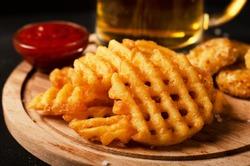 Crispy potato waffles fries, wavy, crinkle cut, criss cross cries with on a cutting board