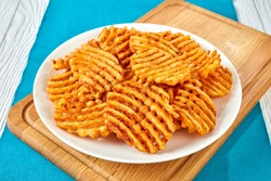 Crispy Potato Waffles Fries, Wavy, Crinkle Cut, Criss Cross Fries on a white plate on a cutting board on a wooden table, view from above, close-up