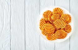 Crispy Potato Waffles Fries, Wavy, Crinkle Cut, Criss Cross Fries on a white plate on a wooden table, view from above, flat lay