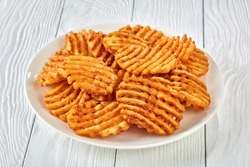Crispy Potato Waffles Fries, Wavy, Crinkle Cut, Criss Cross Fries on a white plate on a wooden table, view from above, close-up