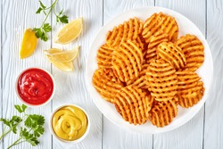 Crispy Potato Waffles Fries, Wavy, Crinkle Cut, Criss Cross Fries on a white plate on a wooden table with mustard and tomato sauce dipping, view from above, flat lay