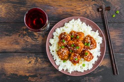 Crispy sesame chicken, chopped breast fillets, with a sticky sweet Asian sauce and white boiled rice on a plate on wooden table, top view.