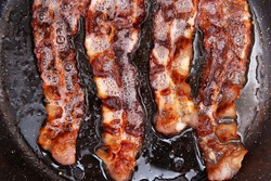 Crispy smokey fried bacon slice or strip. Unhealthy fat food, fattenig ingredient. Red Thin slice or strip or rashers of bacon is fried in a pan, pork fat is melted. High calorie food. Breakfast idea