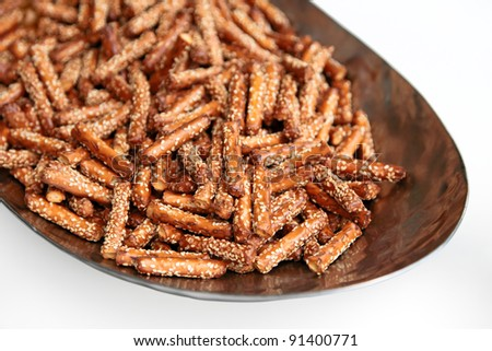 Crispy straw (sticks) with sesame on n a platter isolated on white background