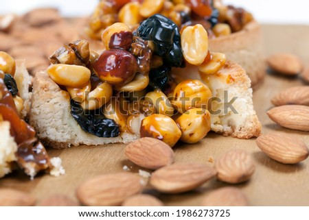crispy tartlet with hazelnuts, peanuts and other ingredients, wheat dough tartlet with nuts and dried fruits in cream caramel, wheat tartlet with sweet filling