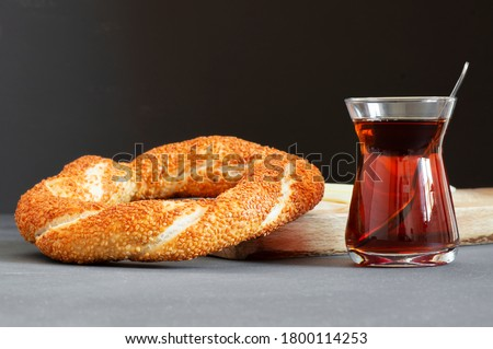 Crispy Turkish traditional bagel / simit with sesame and glass of turkish black tea on rustick background, turkish breakfast pastry concept