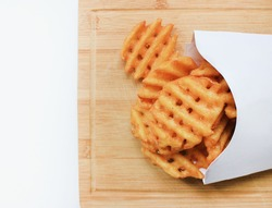 Criss Cut Fries in Take Away White Box on Wooden Board Plate. Fast Food meal freshly made from natural potatoes isolated with empty copy space top view. Unhealthy eating, take out, fast food concept