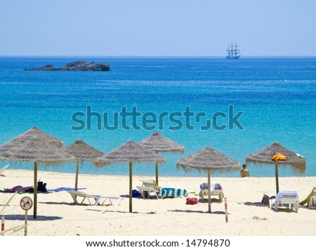 cristal clear waters, with classic sail boat, in sagres beach in the algarve, portugal