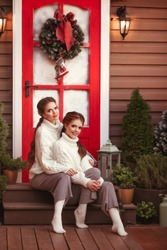 Cristmas portrait of Young Twins Sisters girls in knitted Cozy Sweater sitting on steps by Xmas porch decoration with little trees and lanterns. Two Pretty Women. Best Friends in Stylish Winter Outfit