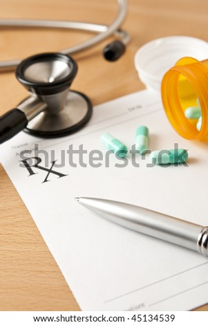 Critical focus on tip of pen. Stethoscope and bottle cap beyond depth of field.