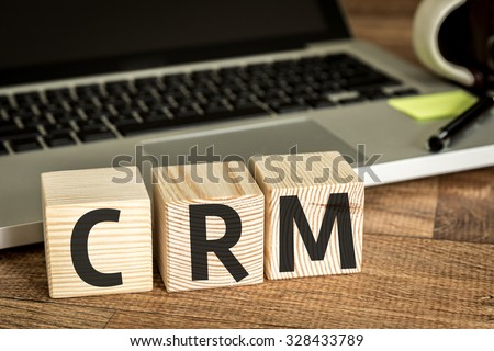 Photo of CRM (Customer Relationship Marketing) written on a wooden cube in front of a laptop