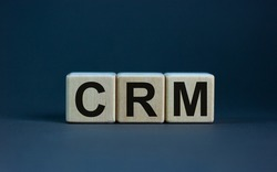 CRM symbol. Concept word 'CRM - customer relationship management' on cubes on a beautiful grey background. Business and CRM - customer relationship management concept.