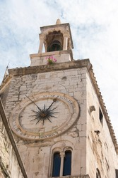 Croatia, Split. Church of Our Lady Bell Tower next to Iron Gate Diocletian Palace. Snapdragons bloom above clock.