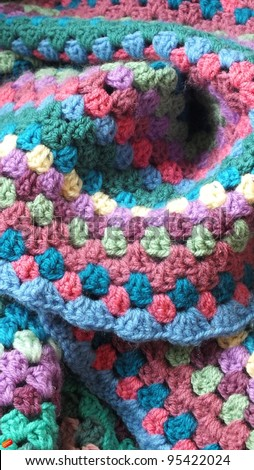 Crochet blanket, a wool handmade afghan blanket, made using granny stitch with blue, pink, cream, green and purple yarn