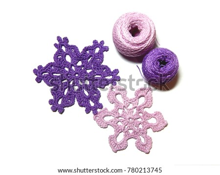 Crochet for design of fir tree or interior. Pink and purple yarn for crocheting christmas decoration on fir tree. Crochet homemade decor for xmas tree. How to make crochet snowflake at home.
