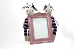 Crochet giraffe girls with pink frame. Cute amigurumi toys. Handmade craft decorations on white background.
