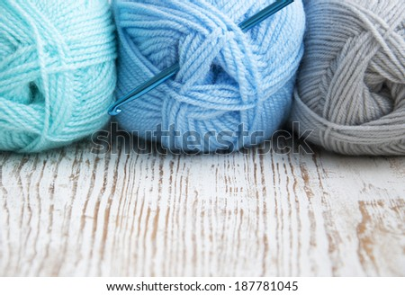 Crochet hook and knitting yarns on a wooden background