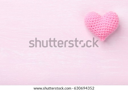 Crochet pink heart on pink wooden background #630694352