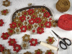 Crochet project of making crochet purse, joining crochet flowers one to another by hand sewing. Concept of art, design, and creativity. Needle, yarns, and scissors are in frame as tools.