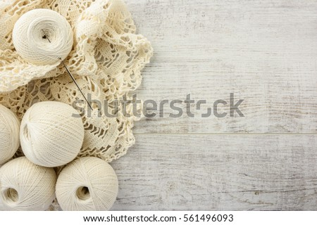 crochet tablecloth, crochet hooks and balls of cotton thread on a white wooden table. top view, copy space #561496093