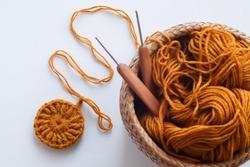Crochet work with cotton yarn, yarn balls and wood crochet needles on white background.