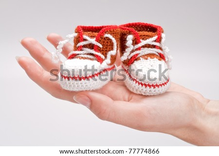 crocheted booties for a boy in the girl's hand