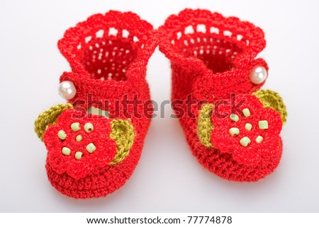 crocheted booties for a girl on a gray background - stock photo