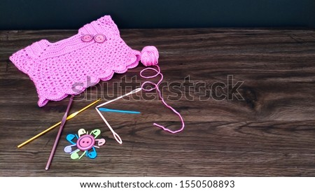 crocheted dress girl with pink yarn ball and crocheting accessories .crocheting accessories are hooks,needlecraft and buttons on a wooden table.close up shot.