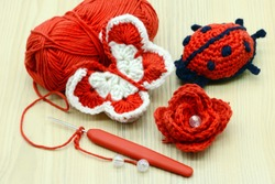 crocheting red white butterfly as well as rose and lady bug with crochet hook and wool