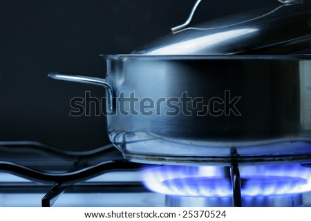 Crock on the gas stove over black background stock photo