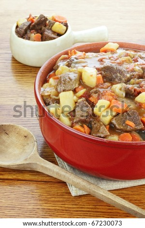 Crock pot full of fresh made roast beef with large chunks of beef, potatoes and carrots.