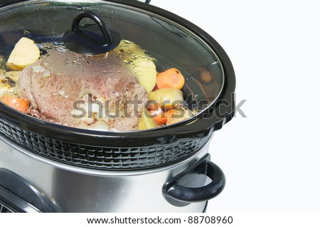 Crock pot with a lightly browned seasoned blade roast with golden potatoes and chopped carrots simmering, isolated on white with copy space.