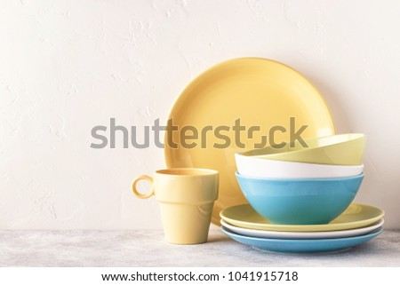 Crockery and cutlery on a light table with copy space.