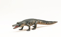 Crocodile is a realistic plastic toy for children. Toy crocodile isolated on white background